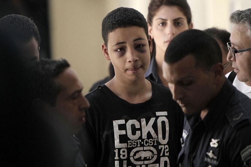 Tariq Abu Khder (centre), a Palestinian-US teenager who was allegedly beaten during police custody, arrives for a hearing at Jerusalem Magistrates Court on July 6, 2014.A Jerusalem court on Sunday, July 6, 2014, ordered Abu Khder to be released