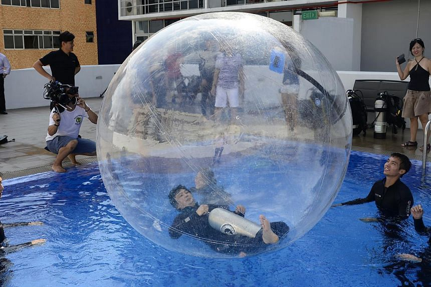 Candidates testing a water balloon at a pool in Geylang last month. They are vying to be the first Singaporean to be launched in a helium stratospheric balloon craft into near-space, more than 20km above sea level, next year.