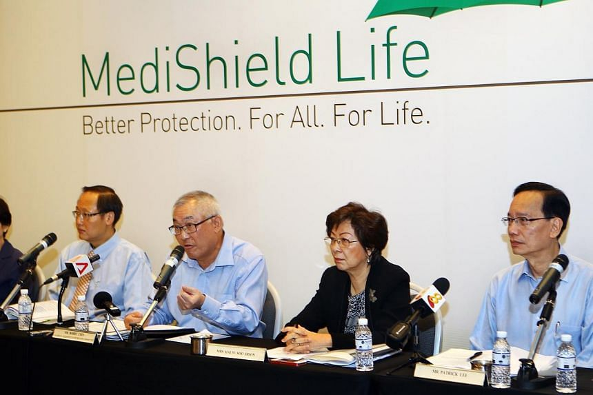 Members of the Medishield Life Review Committee speaking during the press conference held at the Suntec City Convention Centre on June 27, 2014.-- PHOTO: ZAOBAO