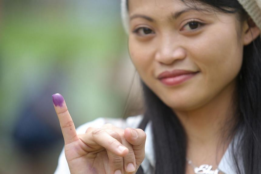 Ekamarliah, 27, a domestic helper, has purple ink on her finger as a mark that she has voted. -- ST PHOTO: ONG WEE JIN