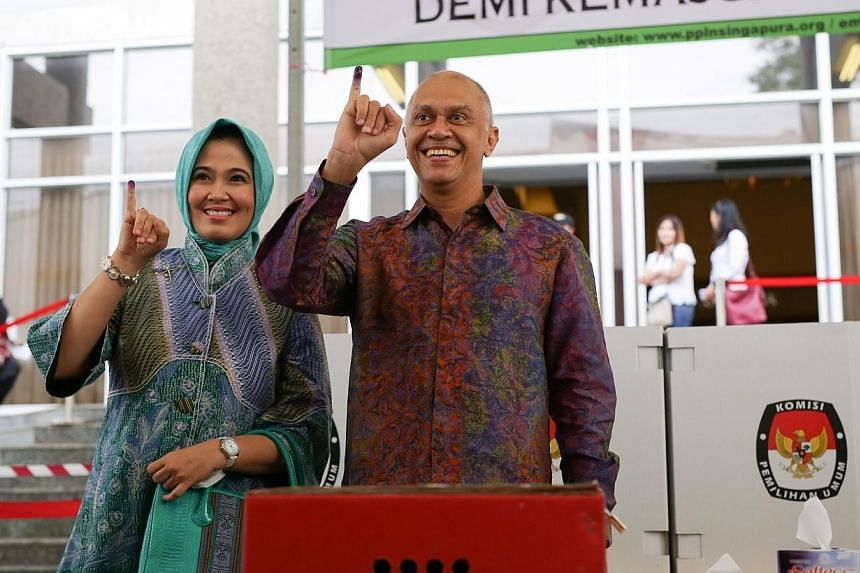 Indonesian ambassador to Singapore Andri Hadi and his wife at the voting booths. -- ST PHOTO: ONG WEE JIN