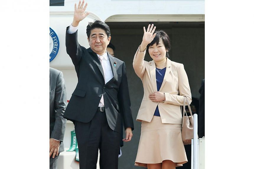 Japanese Prime Minister Shinzo Abe (left), accompanied by his wife Akie, waves as he leaves to New Zealand for his Oceanian tour at Tokyo International Airport on July 6, 2014. Abe started a week-long three nations tour of New Zealand, Australia and