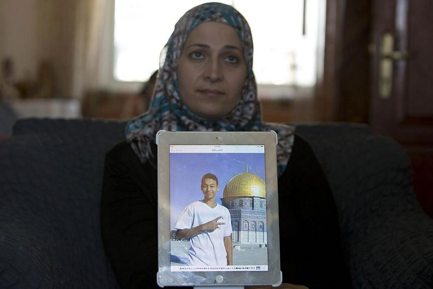 The mother of Tariq Abu Khder (portrait), the 15-year-old cousin of the murdered Palestinian youth Mohammed, shows an old picture of her son, before he was assaulted by Israeli border police in East Jerusalem on July 5, 2014. -- PHOTO: AFP