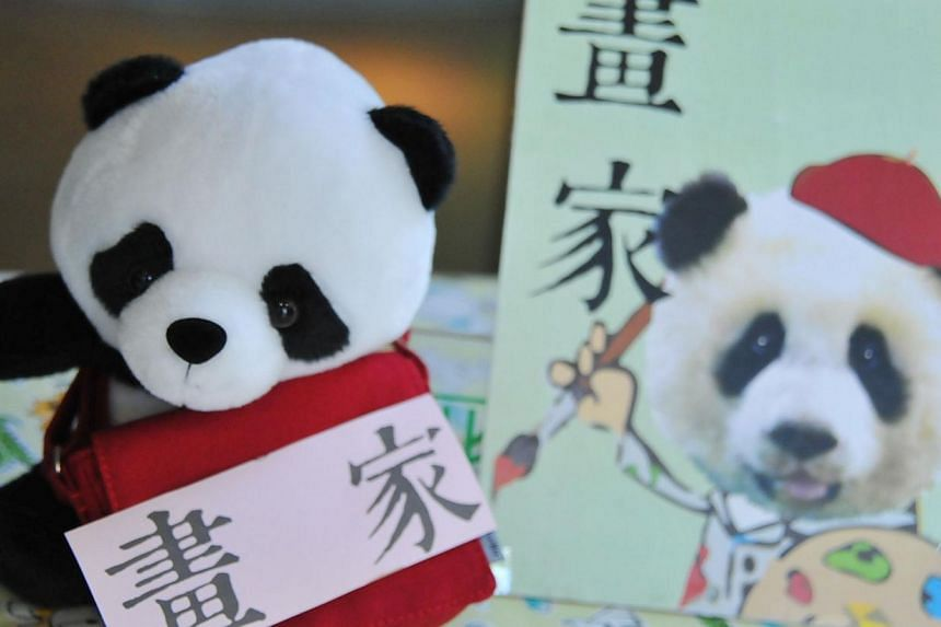 """A career card reading """"painter"""" is the first card Yuan Zai, the first Taiwan-born giant panda, touched and displayed while playing """"Zhua Zhou"""", a traditional game played on a child's first birthday to determine his or her future, during the celebrati"""