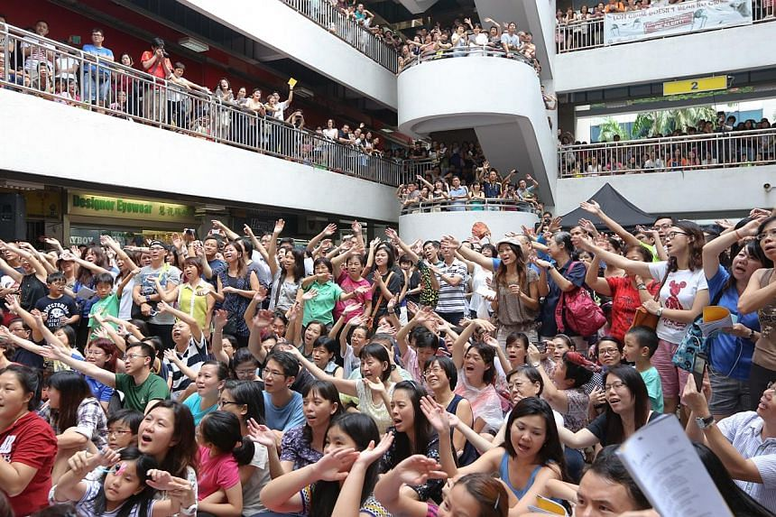 Music lovers who came of age in the 1980s clap, sway and sing along to Singapore-style campus songs on July 6, 2014, at the central atrium of Bras Basah Complex. -- ST PHOTO: ONG WEE JIN