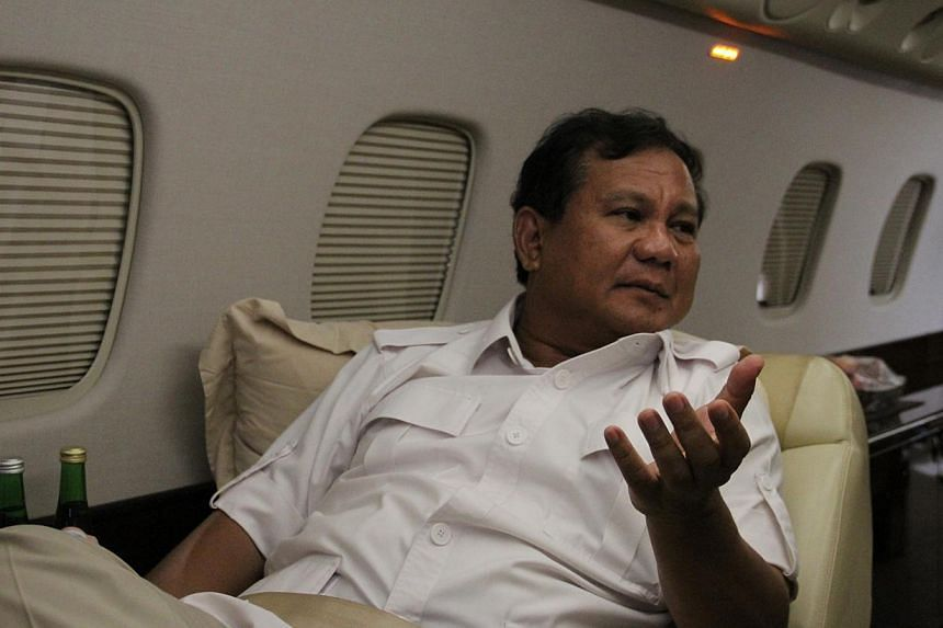 Presidential candidate Prabowo Subianto discusses politics on a private jet to a rally in Semarang, Central Java. He is on the brink of presidency, as surveys now put him within a hair's breadth of his only rival, frontrunner Joko Widodo. -- ST PHOTO