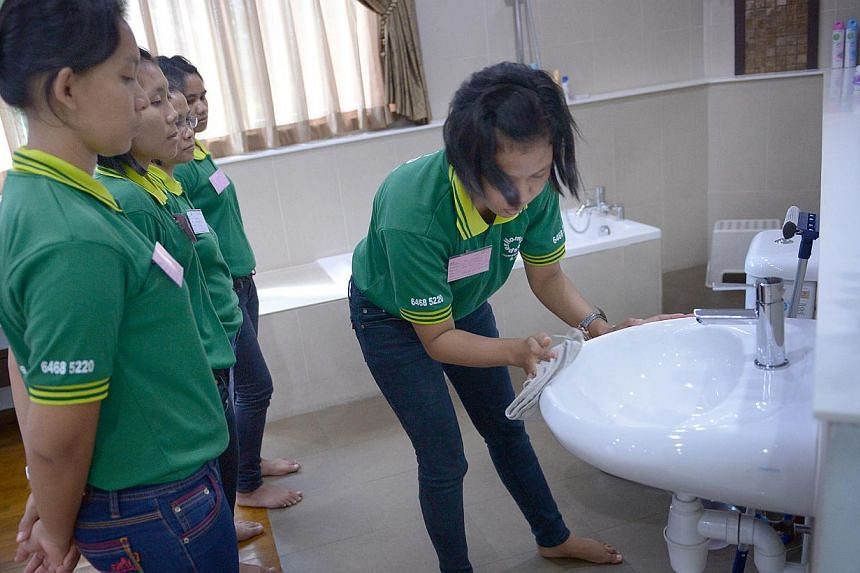Maids being trained in housekeeping chores at a local agency. As a result of the ongoing price war between agencies, maids now pay recruitment fees of more than $4,000 on average, up from $2,200 previously.