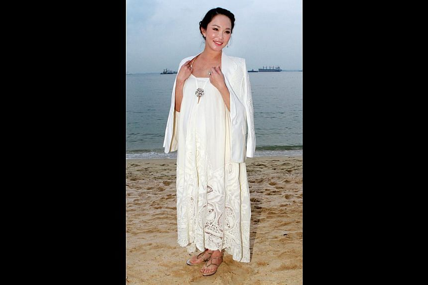 Happy expectations: Fann Wong at the Diner En Blanc picnic on Sentosa (above), her last public appearance before she gives birth, and her nearly nude shot. -- PHOTO: LAU FOOK KONG