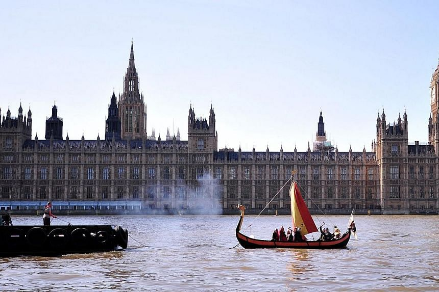 People dressed as a 'Viking warrior-crew' sail along the River Thames near the Houses of Parliament in central London on April 15, 2014.The British government faced growing calls on Sunday for a national inquiry into allegations of child abuse