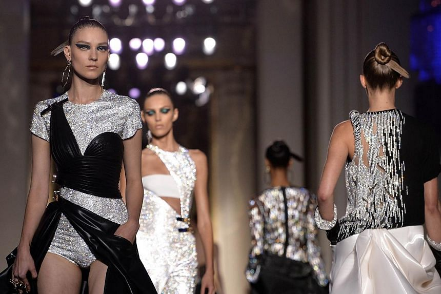 Models present creations by Italian fashion designer Donatella Versace during the 2014/2015 Haute Couture Fall-Winter Versace collection show in Paris on July 6, 2014. -- PHOTO: AFP