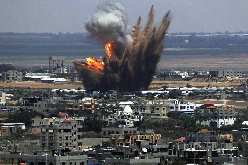 Smoke and flames are seen following what police said was an Israeli air strike in Rafah in the southern Gaza Strip July 8, 2014.Israeli warplanes killed 12 Palestinians Tuesday, pounding the Gaza Strip in a new campaign to stamp out Hamas rocke