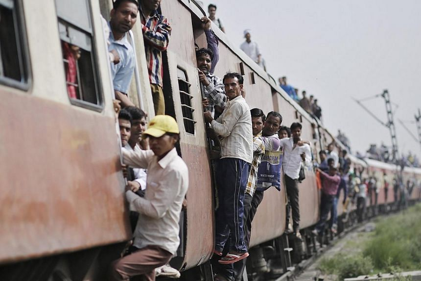 Passengers travel on an overcrowded train at Loni town in the northern Indian state of Uttar Pradesh July 8, 2014. India unveiled plans on Tuesday to open up its railways to foreign investment and introduce the country's first bullet train