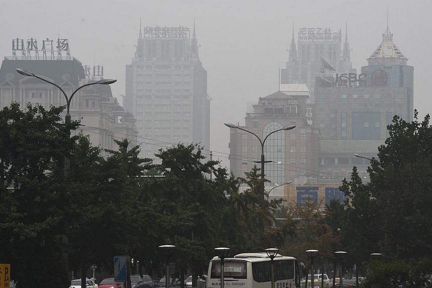 """This photo taken on July 3, 2014 2014 shows buildings through polluted skies in Beijing. Having declared """"war on pollution"""", China is arming itself with tougher weapons from new courts to daily fines and shutting down offenders altogether, in what an"""