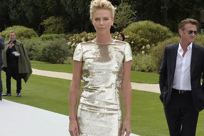 South African actress Charlize Theron and boyfriend US actor Sean Penn upon arrival at the Christian Dior 2014/2015 Haute Couture Fall-Winter collection fashion show in Paris on July 7, 2014. -- PHOTO: AFP