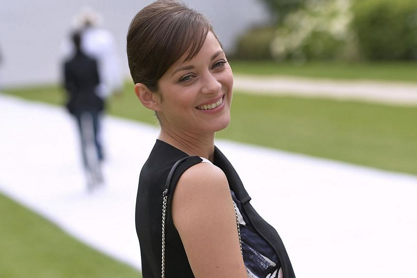 French actress Marion Cotillard poses upon arrival at the Christian Dior 2014/2015 Haute Couture Fall-Winter collection fashion show in Paris on July 7, 2014. -- PHOTO: AFP