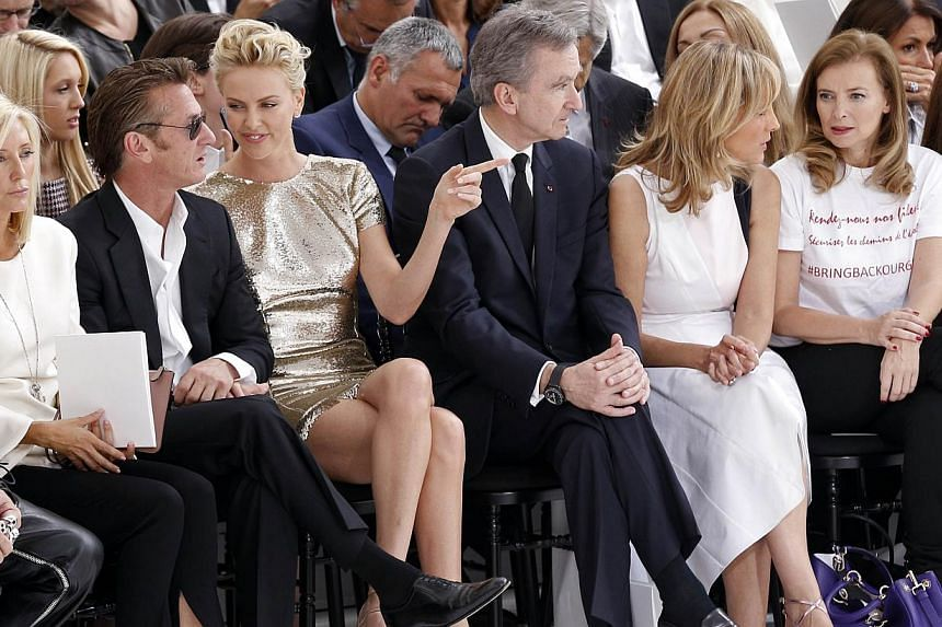(From left) US actor Sean Penn and girlfriend South African actress Charlize Theron, French CEO of LVMH Bernard Arnault and his wife, pianist Helene Arnault, and former companion of France's President Valerie Trierweiler at the Christian Dior 2014/20