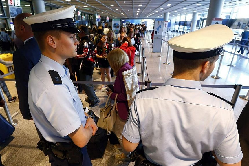 Police officers patrol at a security gate inside the main terminal of Frankfurt Airport on July 3, 2014.Germany has tightened security at its airports after US authorities said they were concerned that Al-Qaeda operatives in Syria and Yemen wer