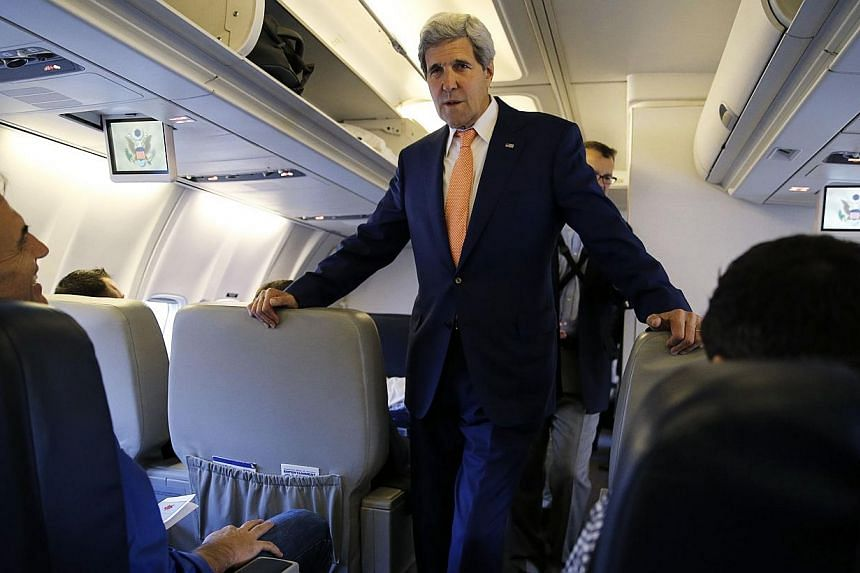 US Secretary of State John Kerry greets media representatives flying aboard his plane bound for diplomatic talks in China while flying out of Washington, DC on July 7, 2014.-- PHOTO: AFP