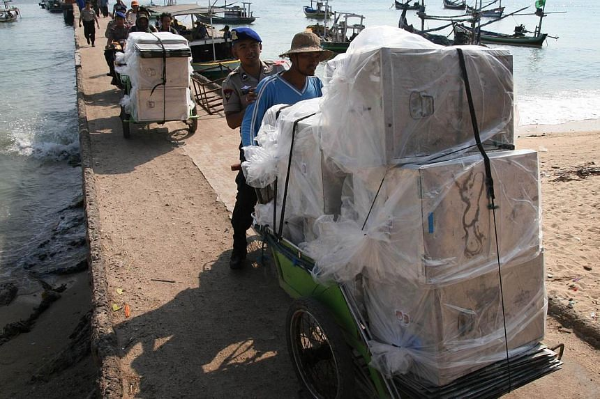 In this photograph taken on July 7, 2014, escorted by police, Indonesian men transport on traditional becak, ballot boxes and polling materials delivered by maritime police boats to Gili Ketapang island located off East Java province ahead of the Jul