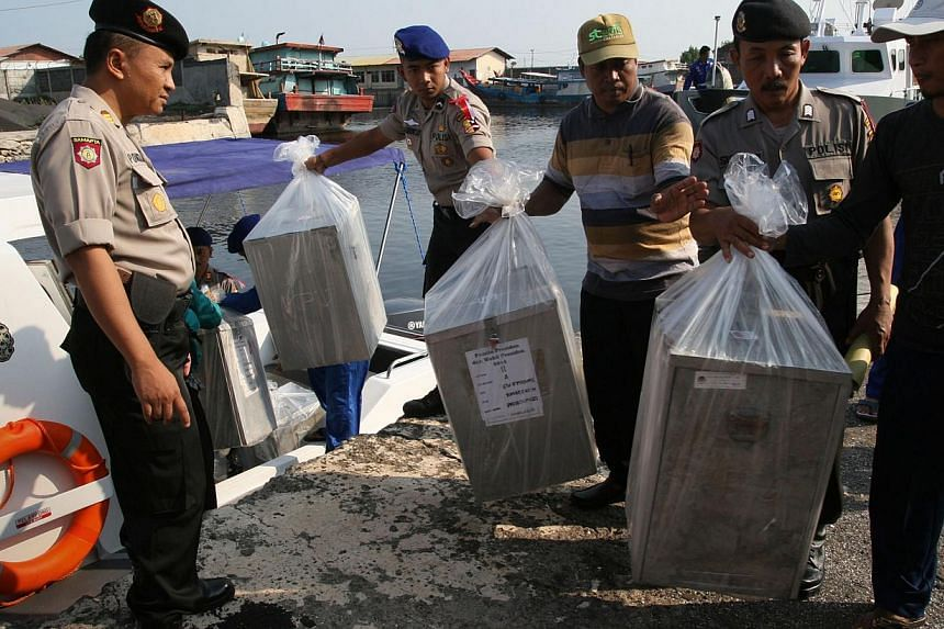In this photograph taken on July 7, 2014, Indonesian police delivers by maritime police boat ballot boxes and polling materials to Gili Ketapang island located off East Java province ahead of the July 9, 2014 presidential election closely contested b