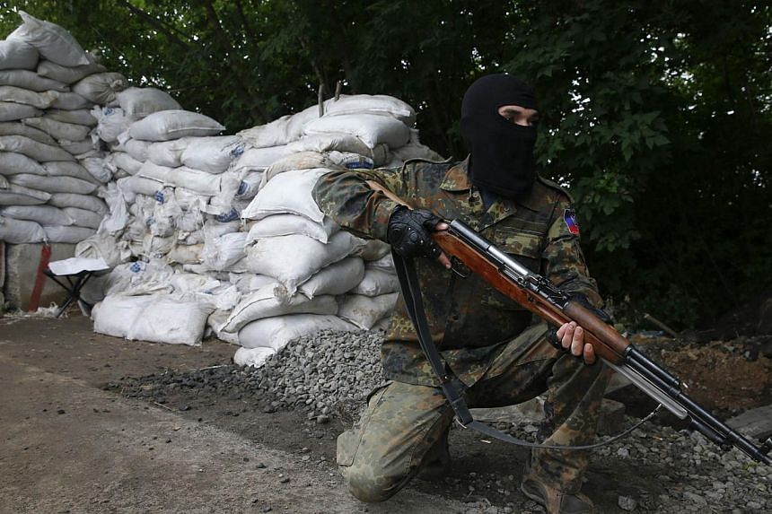 A pro-Russian fighter mans a checkpoint in the eastern Ukrainian city of Donetsk on July 7, 2014. -- PHOTO: REUTERS