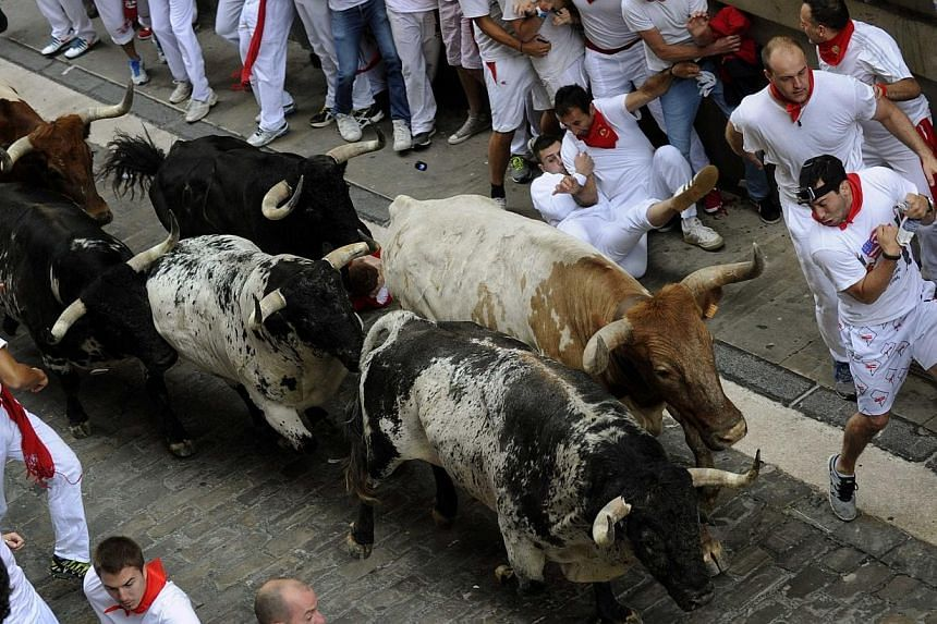 Runners sprint with Torrestrella fighting bulls on Santo Domingo street during the first running of the bulls of the San Fermin festival in Pamplona on July 7, 2014. -- PHOTO: REUTERS
