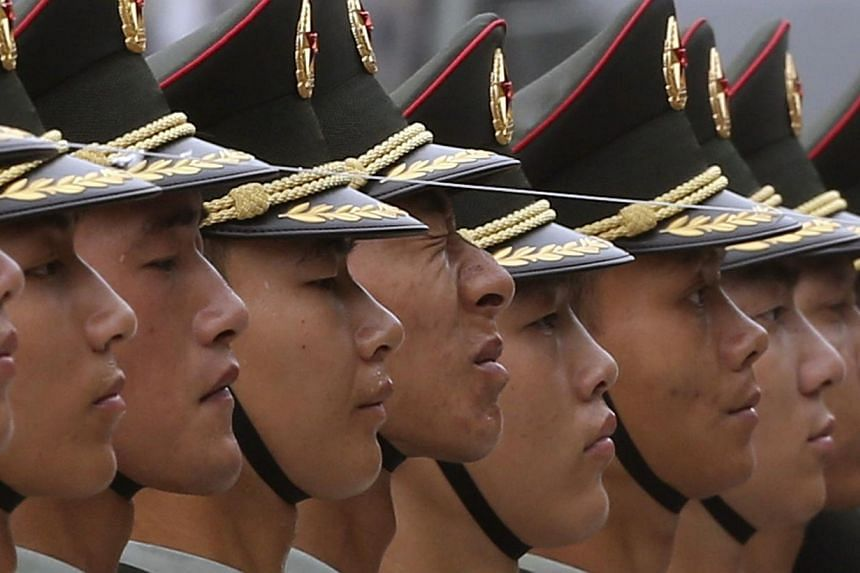 Members of the Chinese PLA honour guard stand behind a string to ensure that they are in a straight line before a welcoming ceremony for Germany's Chancellor Merkel outside the Great Hall of the People in Beijing.  -- PHOTO: REUTERS
