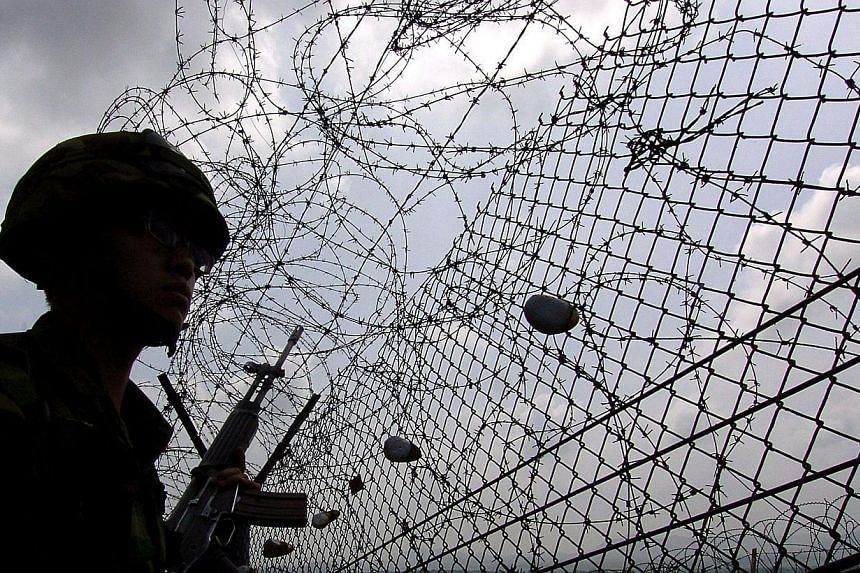 A file photo taken on July 7, 2006, shows a South Korean soldier near the barbed wire of the Demilitarized Zone (DMZ) separating North and South Korea, in Paju.North Korean soldiers have crossed the inter-Korean armistice line into South Korea