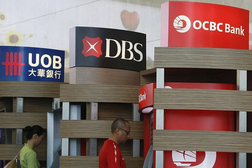 People use Development Bank of Singapore (DBS) and Oversea-Chinese Banking Corp (OCBC) automated teller machines at the airport in Singapore April 30, 2014.Ratings agency Moody's Investors Service has retained its negative outlook on Singapore'