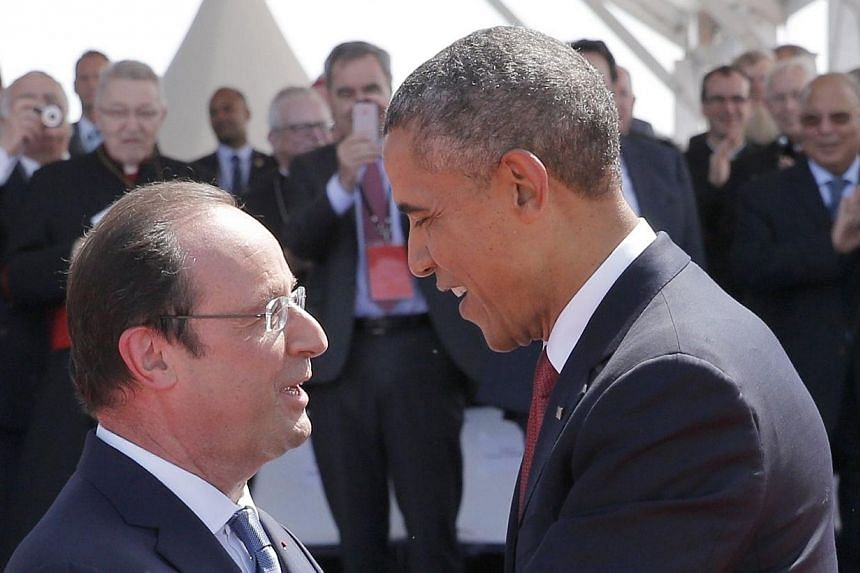 French President Francois Hollande (left) greets US President Barack Obama during an international D-Day commemoration ceremony on the beach of Ouistreham, Normandy, on June 6, 2014, marking the 70th anniversary of the World War II Allied landings in