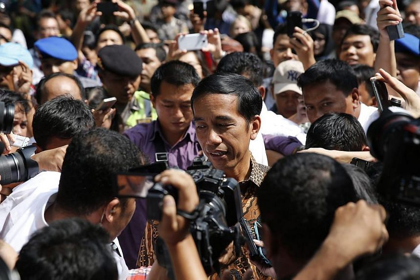 "Indonesian presidential candidate Joko ""Jokowi"" Widodo is surrounded by supporters and members of the media after casting his vote at a polling station in Jakarta on July 9, 2014. -- PHOTO: REUTERS"