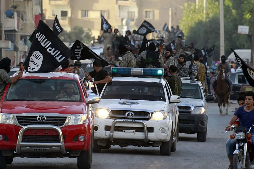 Militant Islamist fighters waving flags, travelling in vehicles as they take part in a military parade along the streets of Syria's northern Raqqa province June 30, 2014. -- PHOTO: REUTERS