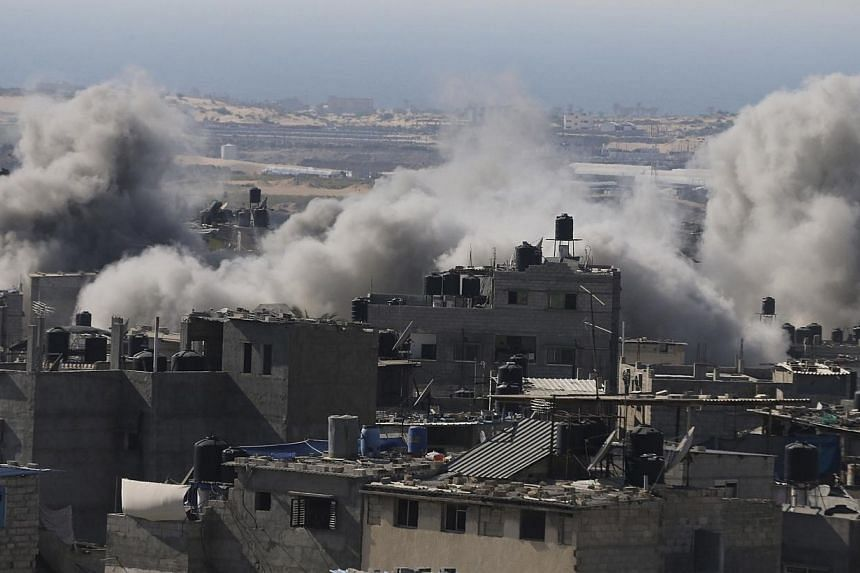 Smoke is seen following what police said was an Israeli air strike in Rafah in the southern Gaza Strip on July 9, 2014. Fifteen women and children were among 22 Palestinians killed in Israeli strikes on Gaza Wednesday, hiking the overall death t
