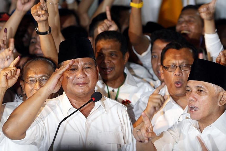Indonesian presidential candidate Prabowo Subianto (left) gives a salute as his vice presidential running mate Hatta Rajasa (right) and supporters gesture after Prabowo declared victory in Jakarta on July 9, 2014. -- PHOTO: REUTERS