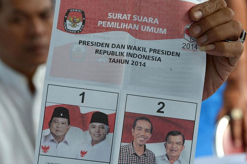 A polling centre official holds up a ballot during a tally of Indonesia's presidential election in Jakarta on July 9, 2014. Uncertainty reigned in Indonesia on Wednesday, July 9, 2014, after both presidential candidates claimed victory in a hard