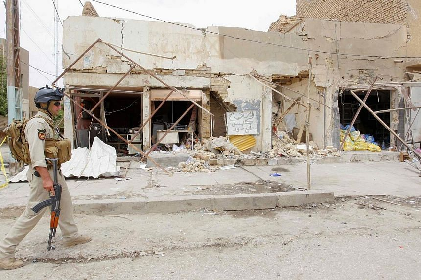 An Iraqi security forces member walks past at the site of a car bomb attack, in the city of Hilla on June 5, 2014.Iraqi security forces found the bodies on Wednesday, July 9, 2014, of 53 men who had been bound and executed, police and medical o