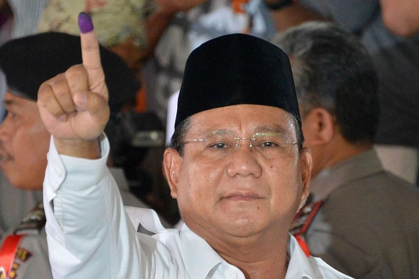 Indonesian presidential candidate Prabowo Subianto displays his inked finger after voting in the country's presidential election at the village of Bojong Koneng in Bogor, West Java province on July 9, 2014. Presidential candidate Prabowo Subianto is