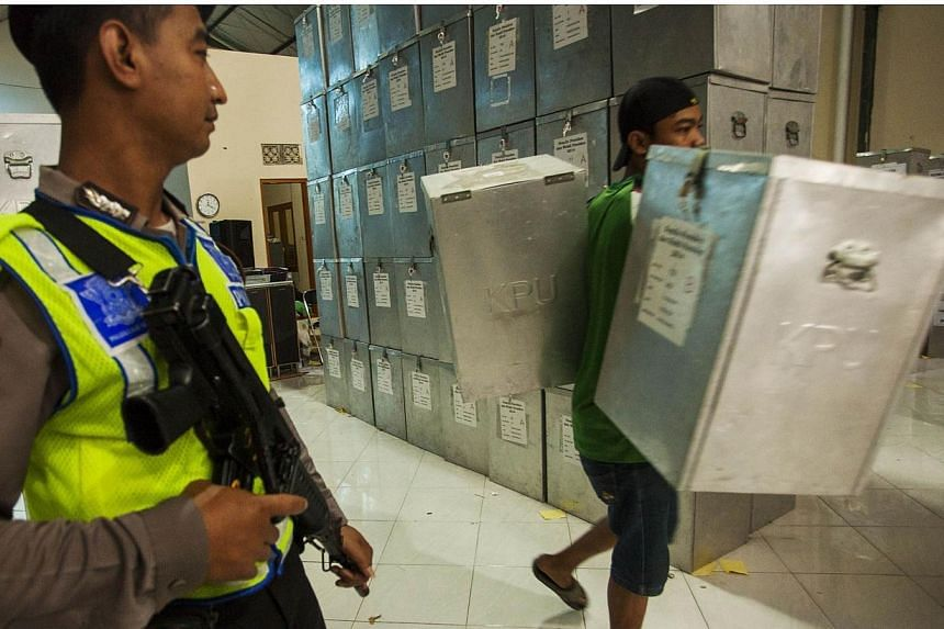 An armed Indonesian policeman watches as a worker carries ballot boxes for distribution to election centers, at the Commission on Election in Yogyakarta, central Java island on July 7, 2014. -- PHOTO: AFP