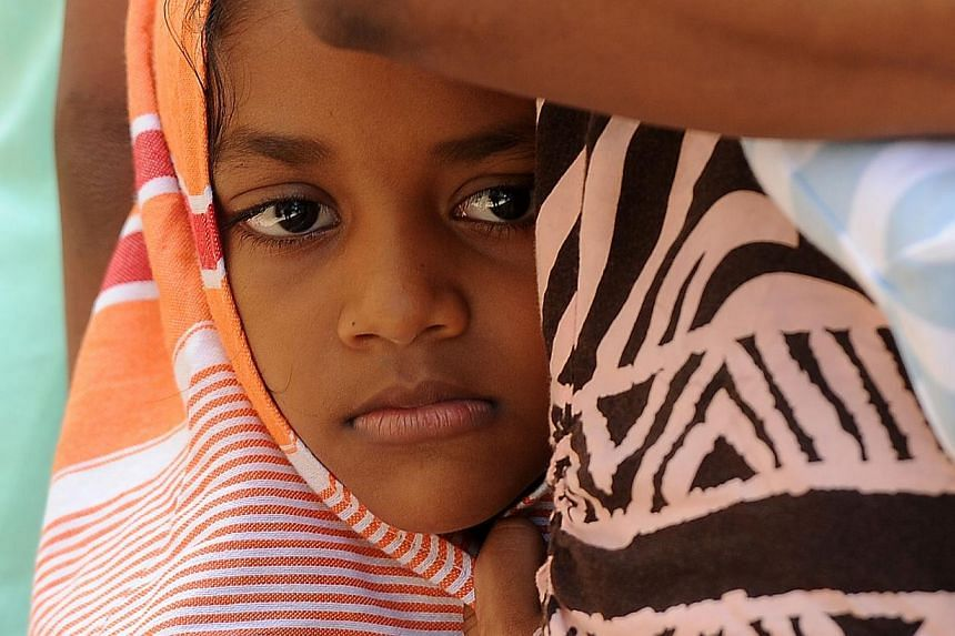 A child among a group of Sri Lankan asylum seekers sent back by Australia looks on before entering the magistrate's court in the southern port district of Galle on July 8, 2014. -- PHOTO: AFP