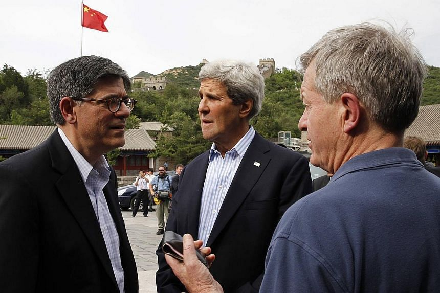 US Secretary of State John Kerry (centre) talks with US Treasury Secretary Jack Lew (left) and US Ambassador to China Max Baucus as they stand in front of a Chinese flag while touring the Badaling section of the Great Wall of China in Beijing,