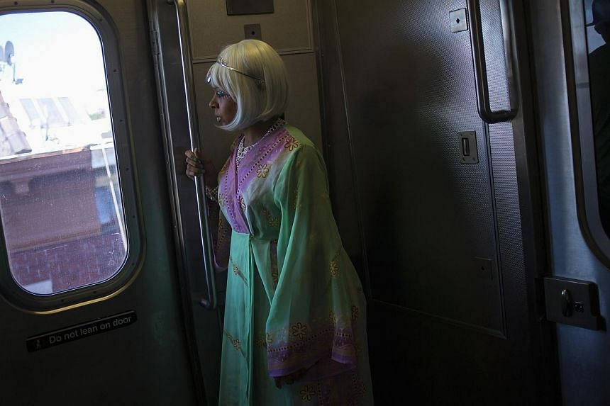 A woman rides the subway before the Mermaid Parade at Coney Island in the Brooklyn section of New York on June 21, 2014. A young homeless woman accused of abandoning her baby on a crowded subway platform in the heart of Manhattan was charged in