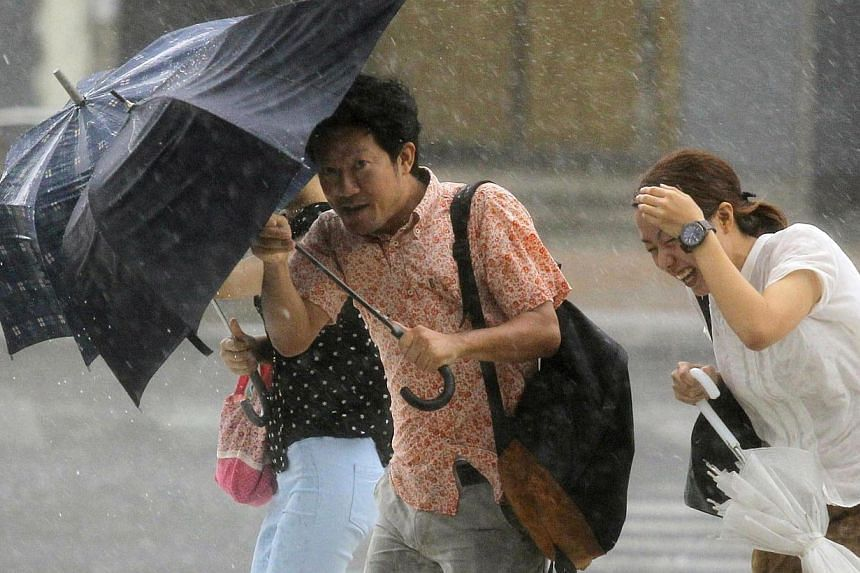 People holding umbrellas walk against strong winds and heavy rain brought about by Typhoon Neoguri on a street in Naha, on Japan's southern island of Okinawa, in this photo taken by Kyodo July 9, 2014. -- PHOTO: REUTERS
