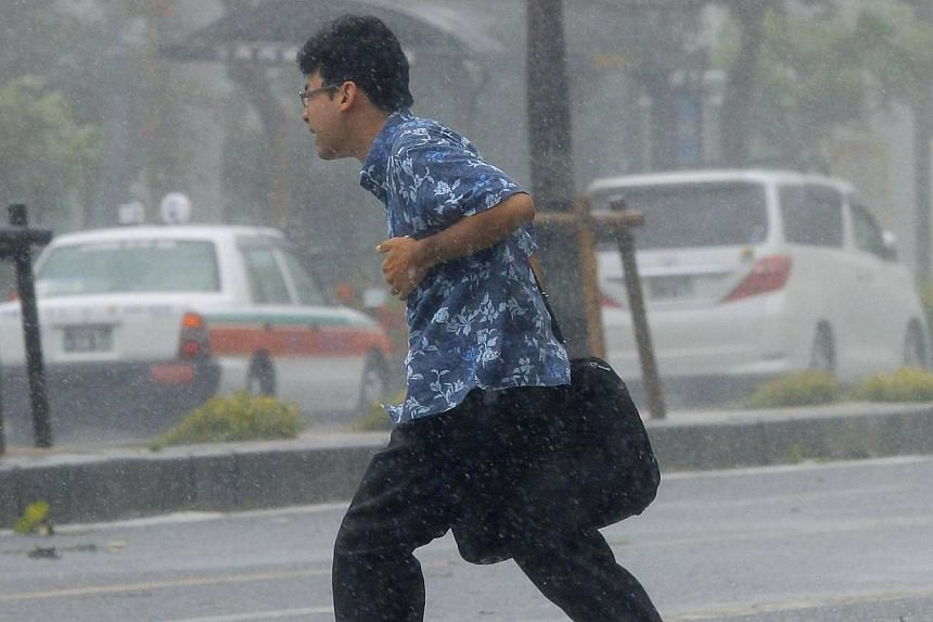 A man walks across a road at a pedestrian crossing amidst strong winds caused by Typhoon Neoguri in Naha, on Japan's southern island of Okinawa, in this photo taken by Kyodo July 8, 2014. -- PHOTO: REUTERS