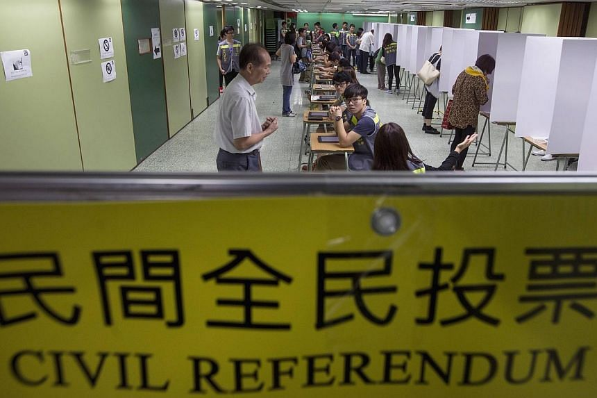 Voters are guided inside a polling station during a civil referendum held by Occupy Central in Hong Kong on June 22, 2014.Beijing has slammed an unofficial referendum on electoral reform to be held in the gambling mecca of Macau, local media sa