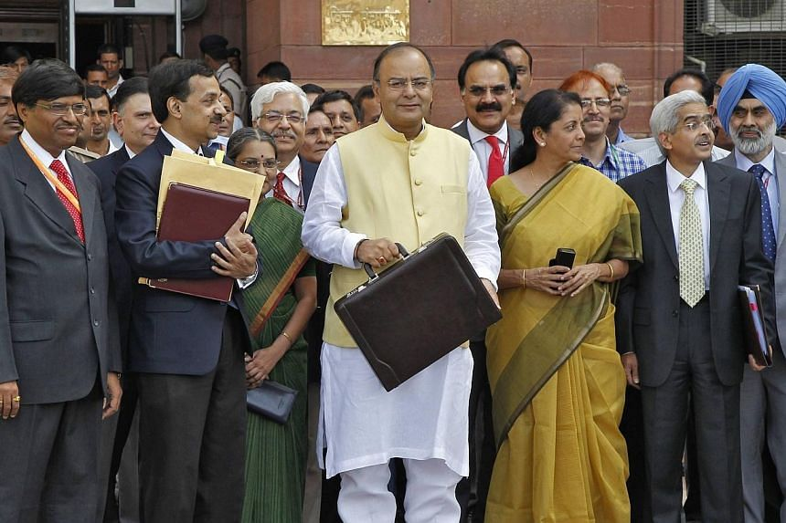India's Finance Minister Arun Jaitley (centre) poses as he leaves his office to present the federal budget for the 2014/15 fiscal year, in New Delhi on July 10, 2014.India's new right-wing government under Prime Minister Narendra Modi u
