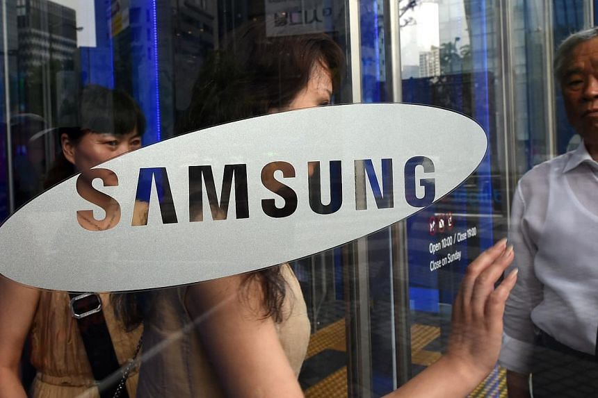 "Visitors walk past a glass door showing the logo of Samsung Electronics at the company's showroom in Seoul on July 8, 2014. Samsung Electronics Co. said on Thursday, July 10, 2014, it was ""urgently"" investigating allegations that one of its suppliers"