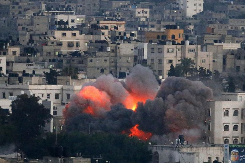 Flames erupt from a building hit by an Israeli air strike on July 9, 2014 in Gaza City. Israeli warplanes pounded Gaza today, killing at least 24 people in a major new confrontation with Palestinian militants, as Hamas flexed its firepower and sent t
