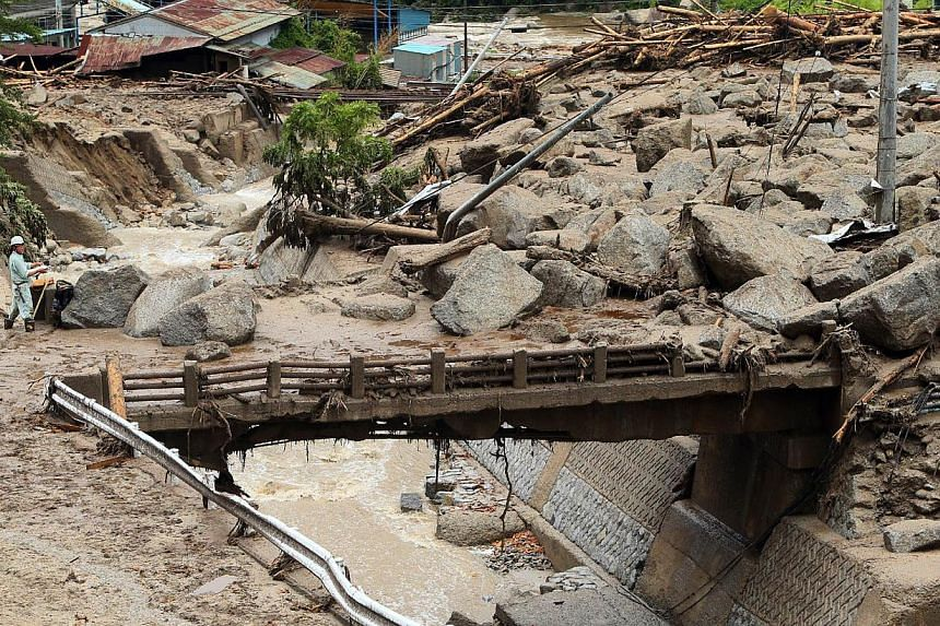 A man (left) stands at the edge of a bridge covered with large boulders and mud spread across a large area after a landslide caused by heavy rains from Typhoon Neoguri in the town of Nagiso in Nagano prefecture, central Japan, on July 10, 2014. -- PH