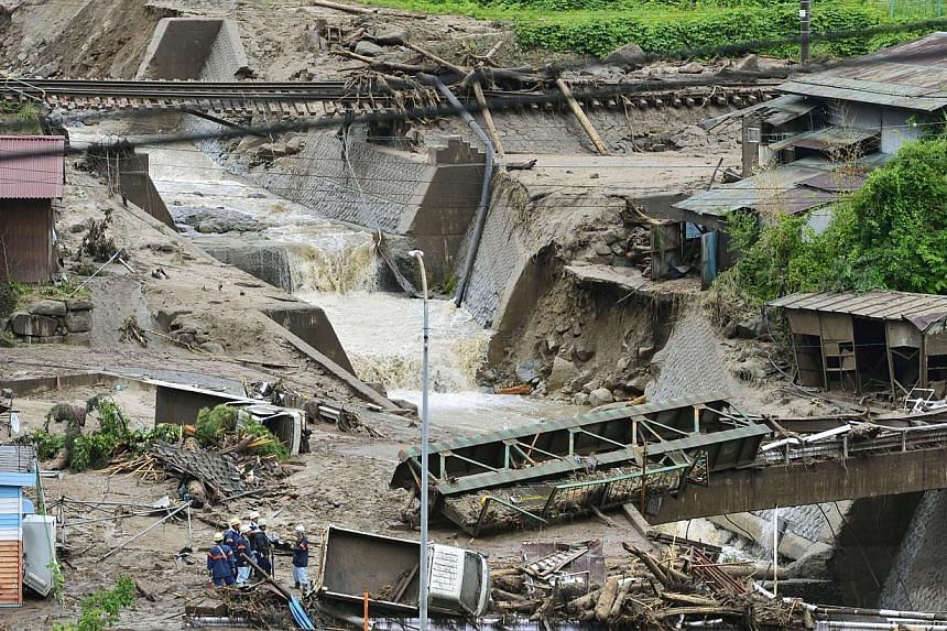 Damaged cars and buildings are seen after a landslide caused by heavy rains due to Typhoon Neoguri in Nagiso town, Nagano prefecture, in this photo taken by Kyodo on July 10, 2014. -- PHOTO: REUTERS