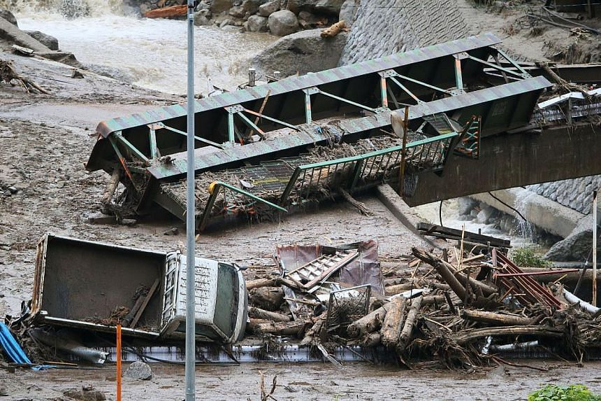 A vehicle, debris and a bridge lie on the bed of the Nashizawa river at Nagiso town in Nagano prefecture, central Japan on July 10, 2014 following a mudslide. The landslide was caused by torrential rain on July 9 brought by Typhoon Neoguri. -- PHOTO: